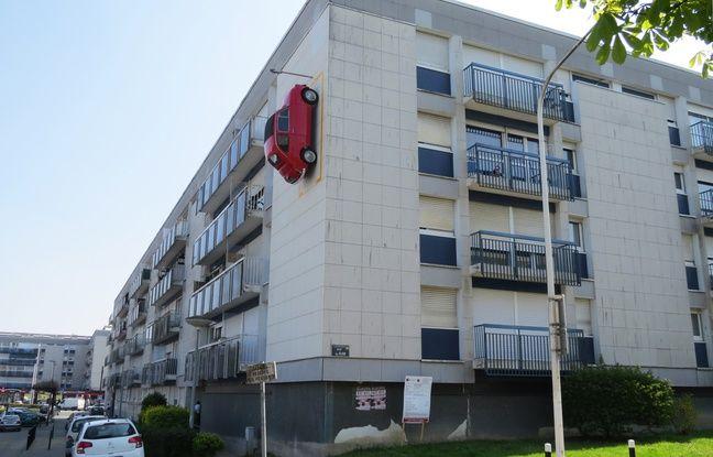 Une Fiat 500 roue est garée à la verticale sur la façade d'un immeuble du quartier Bellevue à Nantes.