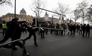 """Des manifestants jettent une barrière en métal sur des policiers lors de la manifestation des """"gilets jaunes"""", samedi, à Paris"""