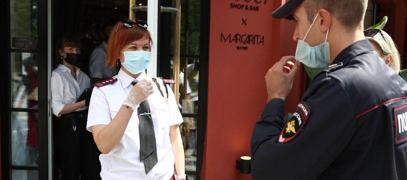 Des policiers ordonnent la fermeture du  Gucci Shop & Bar and Margarita Bistro à Moscou pour violation des règles sanitaires anti-covid, le 15 juin 2021.
