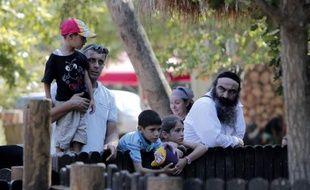 """Zeinab et Tali, agrippées à la rambarde qui les séparent du lac artificiel regardent fascinées, côte-à-côte, les gibbons Siamang suspendus à des lianes, qui accueillent par des cris stridents et des gesticulations les visiteurs du """"zoo biblique"""" de Jérusalem."""