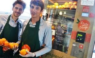 Jonathan et Jérémy, devant leur distributeur de jus d'orange.