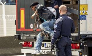 French antirot police (CRS) evacuate a migrant from a Romanian truck on its way to England in the French northern harbour of Calais. The European Commission is ready to discuss new ways to admit and distribute asylum seekers in the EU, its top migration official said on June 3, 2015, after Paris and Berlin urged it to rethink its plans.  AFP PHOTO / PHILIPPE HUGUEN