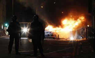 Des agents de police se teinnent près d'une voiture en feu, à Tottenham, au nord de Londres, le 7 août 2011.