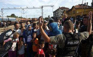 Des migrants face à un policier macédonien, dans la gare ferroviaire de Gevgelija dans le sud de la Macédoine, le 19 août 2015.