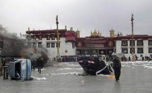 Des tibétains passent devant des voitures renversées et des boutiques en flammes sur la place Barkhor, devant le monastère de Jokhand, vieux de 1400 ans.