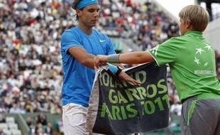 Rafael Nadal récupère sa serviette auprès d'un ramasseur de balle, lors de son match à Roland-Garros contre Pablo Andujar, le 26 mai 2011.