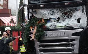 Firefighters stand next to a damaged truck in Berlin, Germany,Tuesday Dec. 20, 2016. The  truck ran into a  crowded Christmas market the evening before and killed several people.  ( Michael Kappeler/dpa via AP)/MBER101/663074166294/1612201231