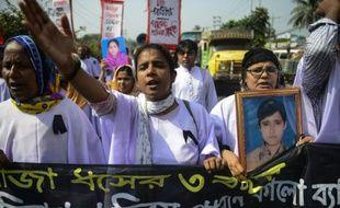 Des ouvriers du textile et des survivants du Rana Plaza défilent aux abords du lieu de la catastrophe qui a fait plus de 1.100 morts en 2013, le 24 avril 2016 à Savar dans la banlieue de Dacca