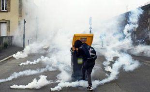 Un participant à la manifestation contre la loi travail se réfugie derrière une poubelle à Rennes, le 17 mai 2016