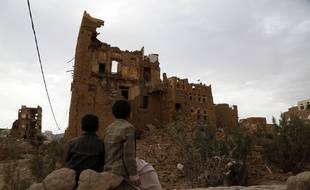 Des enfants au Yémen devant une maison détruite par des bombardements, le 19 mars 2020.