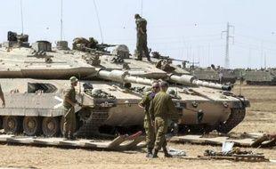 Des soldats israéliens stationnent près de leur char Merkava du coté israélien de la frontière de la bande de Gaza, le 7 juillet 2014