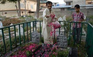 Un Pakistanais répand des pétales de rose sur les tombes de victimes du tremblement de terre de 2005 à Muzaffarabad, dans le Cachemire pakistanais, le 8 octobre 2015