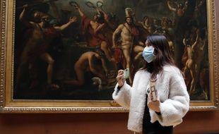 Une touriste, portant un masque, visite le musée du Louvre à Paris, jeudi 5 mars.
