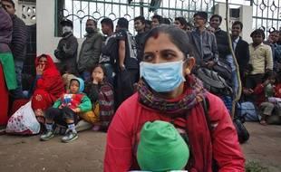 Une femme attend de prendre un bus pour rentrer dans son village, à Katmandou, après le séisme meutrier qui a frappé le Népal le 25 avril 2015.