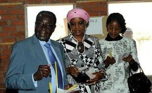 Le président zimbabwéen Robert Mugabe vote avec sa femme et sa fille le 31 juillet 2013 à Harare