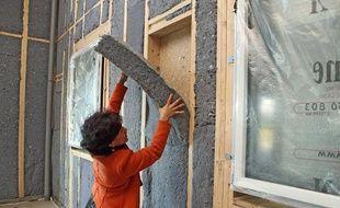 Pose de panneaux d'isolation thermique dans une maison écologique en bois.