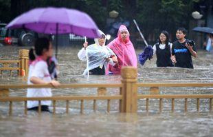 Des gens traversent les eaux de crue le long d'une rue de Zhengzhou, dans la province chinoise du Henan (centre), le mardi 20 juillet 2021.