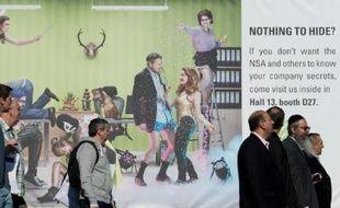 Des visiteurs du Salon high-tech Cebit de Hanovre, en Allemagne, passent devant une publicité pour une société de sécurité informatique, le 10 mars 2014
