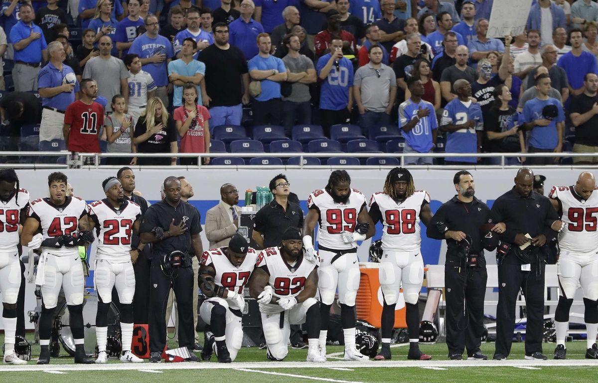 Grady Jarrett et Dontari Poe de l'équipe des Falcons d'Atlanta, un genou à terre durant l'hymne américain.  – Carlos Osorio/AP/SIPA