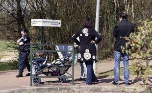 """Un policier et une famille le 24 mars 2015 devant l'école """"Le Mas de la Raz"""" de Villefontaine, dans l'Isère"""