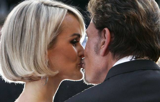 French actor Johnny Hallyday, right, kisses his wife Laeticia Hallyday as they arrive for the screening of the film 'Vengeance' at the 62nd International film festival in Cannes, southern France, Sunday, May 17, 2009.
