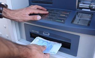 Photo d'illustration d'un homme retirant de l'argent à un distributeur automatique.