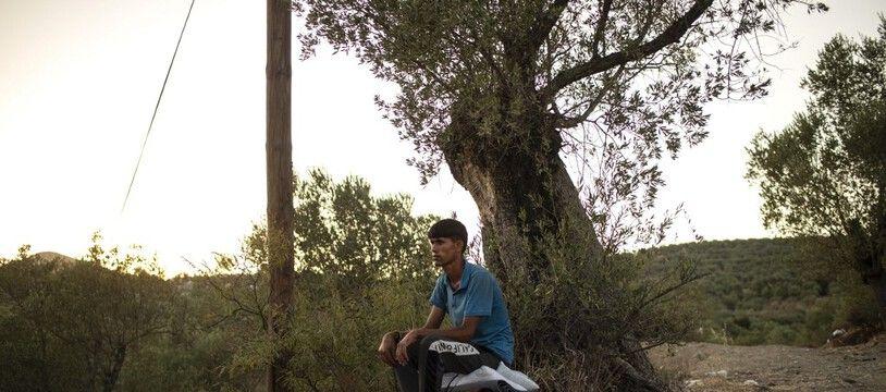 Un homme assis sur ses affaires après l'incendie du camp de Moria, en Grèce, le 14 septembre 2020.