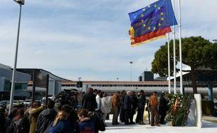 Des proches de victimes du crash de la Germanwings devant la plaque commémorative apposée à l'aéroport de Barcelon à El Prat de Llobregat, le 23 mars 2016