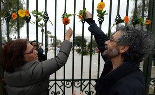 Des Tunisiens accrochent des fleurs le 24 mars 2015 sur les grilles du Musée du Bardo à Tunis, en souvenir des victimes de l'attentat jihadiste qui a fait 21 morts