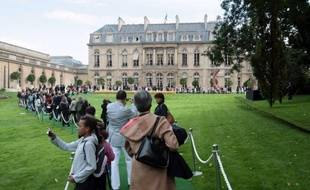 """Visitors queue up in the Elysee gardens to visit the Elysee presidential palace on September 19, 2009 at the beginning of the European Heritage Days, which take place on September 19-20. Background at right, a 2004 sculpture by Jean-Baptiste Boiteux and Nicolas Polowski : """"C'est ineluctable, il va tomber"""" (Sure, it will fall down), center, a Charles Henri Fertin work, """"22032"""", displayed for the event. AFP PHOTO JACQUES DEMARTHON"""