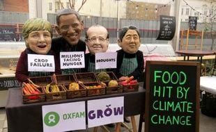 Photo de l'ONG Oxfam le 10 novembre 2013 à Varsovie de manifestants portant des masques d'Angela Merkel, Barack Obama, François Hollande et Shinzo Abe, dans le cadre d'une campagne pour dénoncer l'impact du changement climatique sur l'agriculture