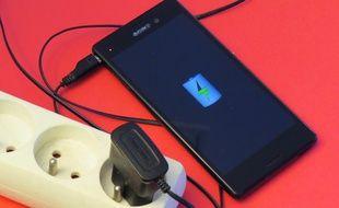 Un téléphone portable, en charge, branché à une prise secteur (illustration).