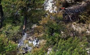 Les pompiers tentent d'éteindre un incendie sur l'épave d'un Mirage 2000-B de la base aérienne d'Orange qui s'est écrasé lundi 4 aout 2014 sur la commune de Viens (Vaucluse) durant un exercice. Les deux pilotes ont eu le temps de s'éjecter.