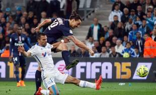 Paris Saint Germain's Swedish forward Zlatan Ibrahimovic, top, challenges for the ball with Marseille's French defender Jeremy Morel during the League One soccer match between Marseille and Paris Saint-Germain, at the Velodrome Stadium, in Marseille, southern France, Sunday, April 5, 2015. (AP Photo/Claude Paris)/MAR136/811513733979/1504052317