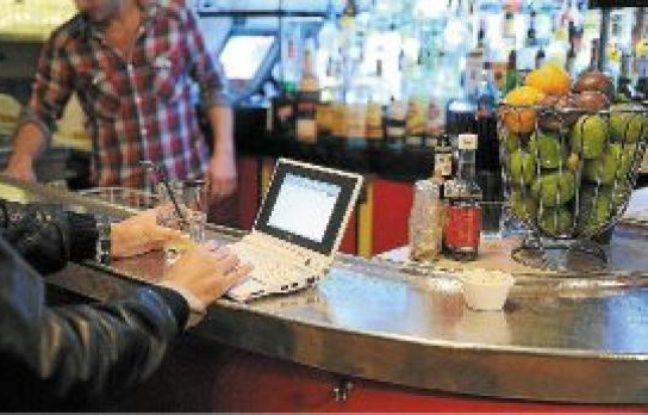 Un consommateur utilise son netbook (mini-PC) dans un café parisien.