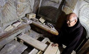 Le 28 octobre 2016, un Franciscain regarde la tombe où aurait été déposé le corps de Jésus alors que la plaque qui la recouvrait a été déplacée en vue de travaux scientifiques...