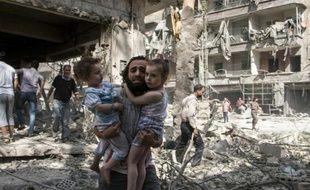 Un Syrien transporte ses deux petites filles au milieu des ruines après une attaque au baril de dynamite dans un quartier d'Alep tenu par les rebelles le 17 septembre 2015