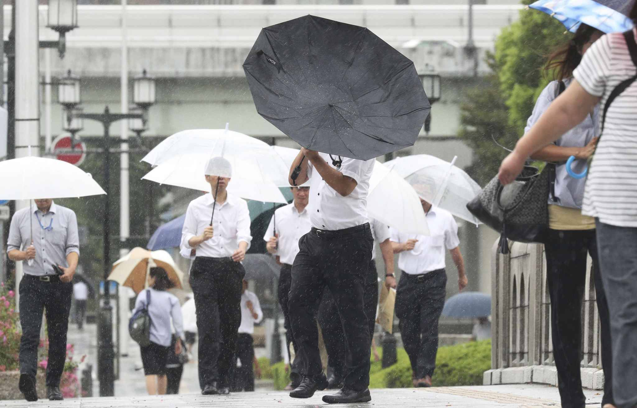 People try to hold umbrellas in strong wind triggered by Jebi in Osaka on Sep.4, 2018. Powerful typhoon made a landfall on Tokushima Prefecture in noon and expected to proceed to the Sea of Japan. Violent winds, high waves and heavy rains are forecasted in wide area of Japan till next day.