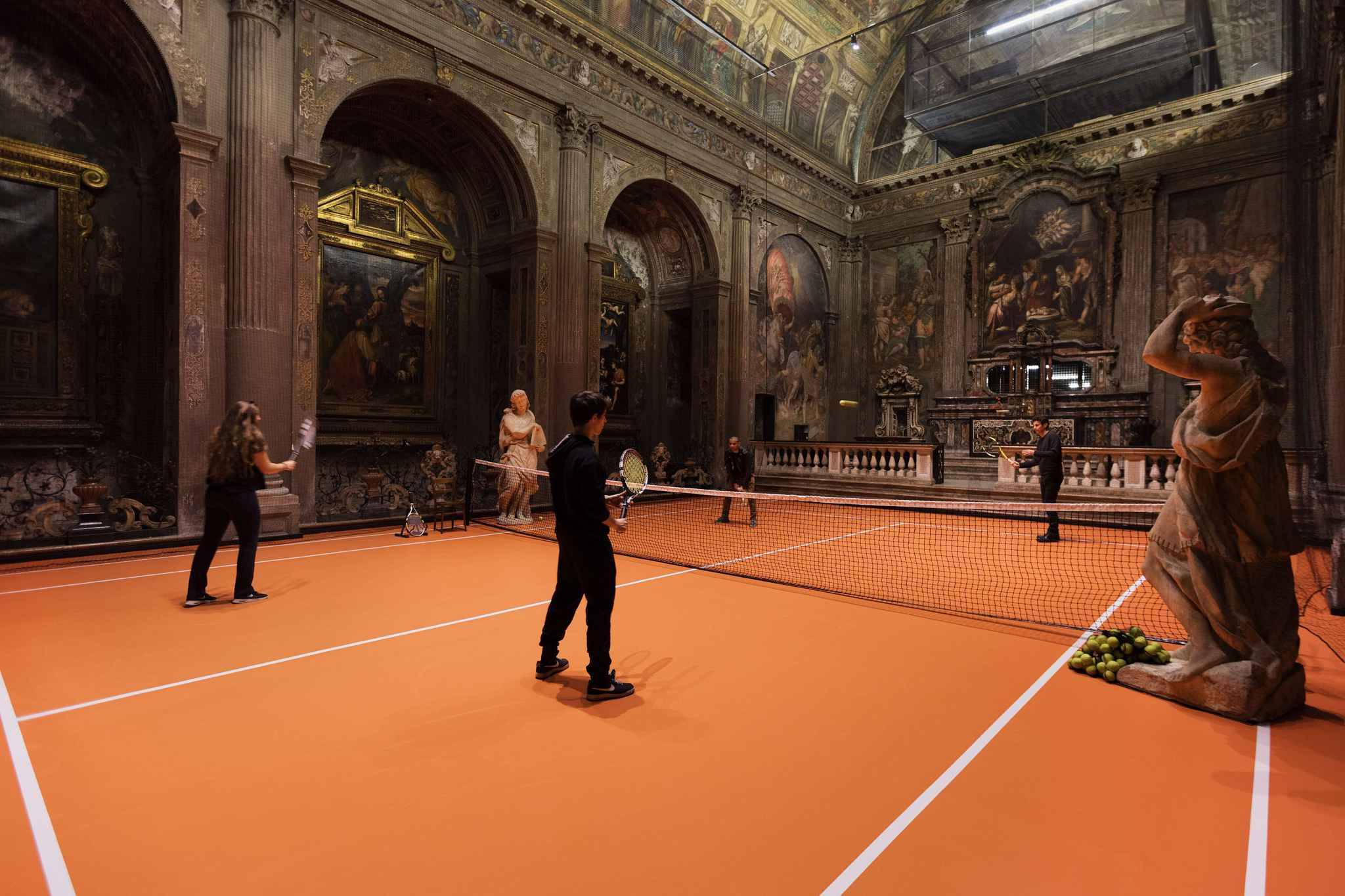 """An artist has transformed the floor of Milan's San Paolo Converso church into a fully functioning tennis court where anyone can play.  Created by New York based artist Asad Raza, the floor, net, rackets, tennis balls, iced tea, and coaches are all part of an interactive art piece named Untitled (Plot for Dialogue), which encourages visitors to play tennis in the beautiful church.  Raza's aim is to fill the space with a new social practice not of receiving messages from on high, but engaging in a two-way exchange and play of equals.  """"For Raza, the game serves as a method of absorbing energetic drives into symbolic but non-harmful practices,"""" reads a description of the piece. """"Visitors become more than spectators - practicing with the coaches, the inhabit their bodies in coordinated action.""""  Erected between 1549 and 1610, the church's frescos display the work of Giulio and Antonio Campi and depict the life of Paul the Apostle. The church was deconsecrated in 1808 following a decree issued by Napoleon and was used as a storage space until 1932, when it was renovated to become a concert hall. The space was also used as a recording studio between the 1960s and the 1980s.  The exhibition is running until 16 December and is free and open to the public from Thursday to Saturday. More information on Untitled (Plot for Dialogue) is available at the Converso website http://www.converso.online.  Where: Milan, Italy When: 16 Nov 2017 Credit: Asad Raza/San Paolo Converso/Cover Images  **EDITORIAL USE ONLY. IMAGES ONLY TO BE USED IN CONJUNCTION WITH EDITORIAL STORY. IMAGE COPYRIGHT REMAINS WITH THE PHOTOGRAPHER AND/OR SUPPLIER.**/COVER33326374/EDITORIAL USE ONLY. IMAGES ONLY TO BE USED IN CONJUNCTION WITH EDITORIAL STORY. IMAGE COPYRIGHT REMAINS WITH THE PHOTOGRAPHER AND/OR SUPPLIER./1711161842"""