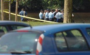 Le tronc d'une femme dans une valise a été découvert mardi soir, dans la Sèvre, sur la commune du Vertou, au sud de Nantes. ici, les enquêteurs de la section de recherche d'Angers et les gendarmes sur place, le 11 juin 2008.