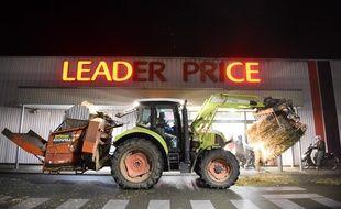 Un tracteur dépose du foin devant un Leader Price à Allonnes, près du Mans lors d'une manifestation d'agriculteurs en novembre 2017.