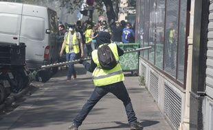 Des manifestants «gilets jaunes» tentent de briser une vitrine à Paris, le 20 avril 2019.