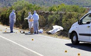 Policiers et enquêteurs examinent la scène du crime à côté de Urtaca en Corse du sud, le 17 août 2014