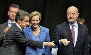 Nicolas Sarkozy (à g.) et Alain Juppé (à d.) entourent Virginie Calmels, candidate LR aux élections régionales en Aquitaine-Limousin-Poitou-Cahrentes, lors d'un meeting donné à Limoges le 14 octobre 2015. AFP PHOTO / NICOLAS TUCAT