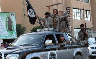 Image fournie par le média jihadiste Welayat Raqa le 30 juin 2014 montrant des jihadistes du groupe Etat islamique paradant dans une rue de la ville syrienne de Raqa