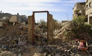 """Le cadre de la porte où Banksy auraitpeint «Bomb Damage», au milieu des ruines à l'est de Jebaliya, au nord de la bande de Gaza. Tuesday, March 31, 2015. Artworks by the elusive British graffiti artist Banksy are typically sold for hundreds of thousands of dollars, but in the Gaza Strip a local painter has succeeded in purchasing a Banksy original for less than $200. The popular street artist is believed to have sneaked into Gaza in February, leaving behind four murals including one drawn on a metal door that depicted a Greek goddess cowering against the rubble of a destroyed house. The painting of the goddess Niobe, titled """"Bomb Damage,"""" was drawn on the lone remaining part of a two-story house belonging to the Dardouna family in Jabaliya, northern Gaza Strip. (AP Photo/Adel Hana)"""