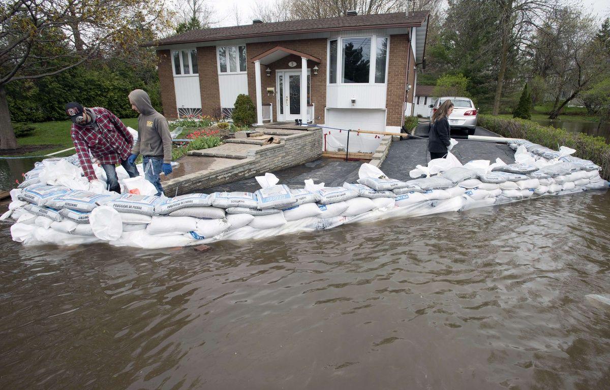 Des habitants de l'île Bizard, près de Montréal, protègent leur maison avec des sacs de sable ce lundi 8 mai 2017, alors que le Canada connaît ses pires inondations depuis une demi-siècle. – Paul Chiasson/AP/SIPA