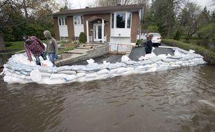 Des habitants de l'île Bizard, près de Montréal, protègent leur maison avec des sacs de sable ce lundi 8 mai 2017, alors que le Canada connaît ses pires inondations depuis une demi-siècle.