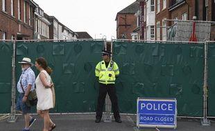 Un agent de police britannique se tient devant une palissade érigée sur Rollestone Street, à Amesbury,  le 5 juillet 2018, du fait de l'enquête sur l'empoisonnement d'un couple au Novitchok.