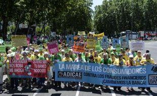 """Au son des sifflets et des couvercles de casseroles, plusieurs centaines de personnes ont défilé samedi à Madrid pour dénoncer """"la fraude et les abus bancaires""""."""